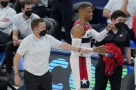 Washington Wizards head coach Scott Brooks, left, holds back guard Russell Westbrook, right, as he gestures towards the Oklahoma City Thunder bench in the second half of an NBA basketball game, Friday, April 23, 2021, in Oklahoma City. (AP Photo/Sue Ogrocki)