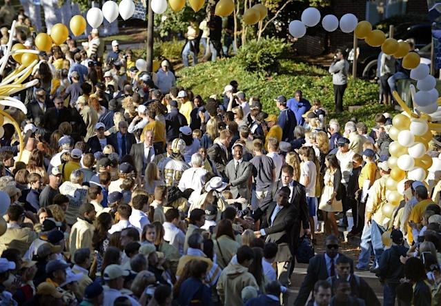 Georgia Tech football players are greeted by students and fans as they walk through the area known as Yellow Jacket Alley to enter Bobby Dodd Stadium for an NCAA college football game against Pittsburgh on Saturday, Nov. 2, 2013, in Atlanta. (AP Photo/David Tulis)