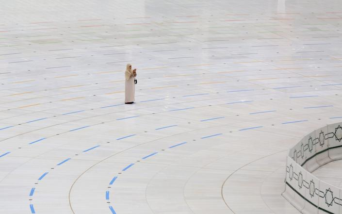A woman stands on a ring delineating where worshippers can stand around the Kaaba in Mecca - GETTY IMAGES