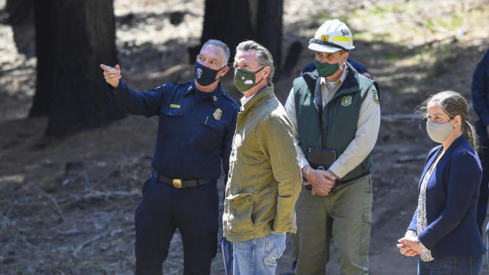 Gov. Gavin Newsom meets with local fire officials while touring an area burned by last year's Creek Fire near Shaver Lake in Fresno County, Calif., Thursday, April 8, 2021. California will authorize $536 million for wildfire mitigation and forest management projects before the worst of the fire season strikes later this year, Newsom and legislative leaders said Thursday. (Craig Kohlruss/The Fresno Bee via AP)
