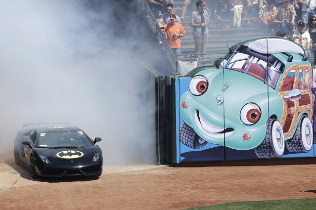 The Batmobile drives into AT&T Park with Miles Scott, dressed as Batkid, who threw out the ceremonial first pitch before an opening day baseball game between the San Francisco Giants and the Arizona Diamondbacks in San Francisco, Tuesday, April 8, 2014. On Nov. 15, 2013, Scott, a Northern California boy with leukemia, fought villains and rescued a damsel in distress as a caped crusader through The Greater Bay Area Make-A-Wish Foundation. (AP Photo/Jeff Chiu)