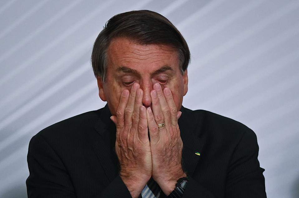 "BRASILIA, BRAZIL - DECEMBER 09:  President of Brazil Jair Bolsonaro reacts during the opening ceremony of the forum ""The Control in Combating Corruption"" amidst the Coronavirus (COVID - 19) pandemic at Planalto Palace on December 09, 2020 in Brasilia. Brazil has over 6.674,000 confirmed positive cases of Coronavirus and has over 178,159 deaths. (Photo by Andre Borges/Getty Images)"