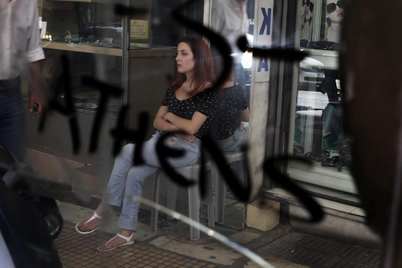 A woman is reflected in a graffiti-covered mirror as she waits for customers outside her sign-making shop in central Athens on Thursday, Aug. 30, 2012. Greek Prime Minister Antonis Samaras promised his austerity-weary countrymen on Thursday that new spending cuts planned for 2013-14 will be the last, but warned that without them the nation would have to leave the 17-member eurozone. (AP Photo/Petros Giannakouris)