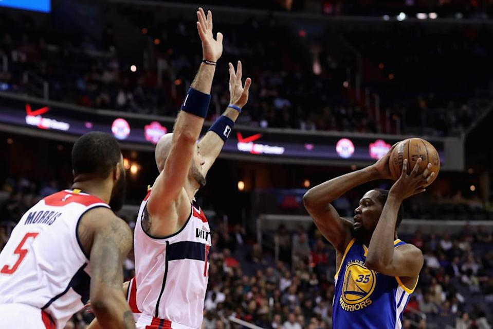 Kevin Durant (right) looks to pass around Marcin Gortat of the Washington Wizards (AFP Photo/Rob Carr)