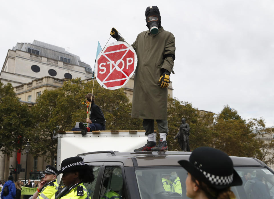 A man wearing a gas mask stand on top of a car as other demonstrators block Trafalgar Square in central London Monday, Oct. 7, 2019. Extinction Rebellion movement blocked major roads in London, Berlin and Amsterdam on Monday at the beginning of what was billed as a wide-ranging series of protests demanding new climate policies. (AP Photo/Alastair Grant)