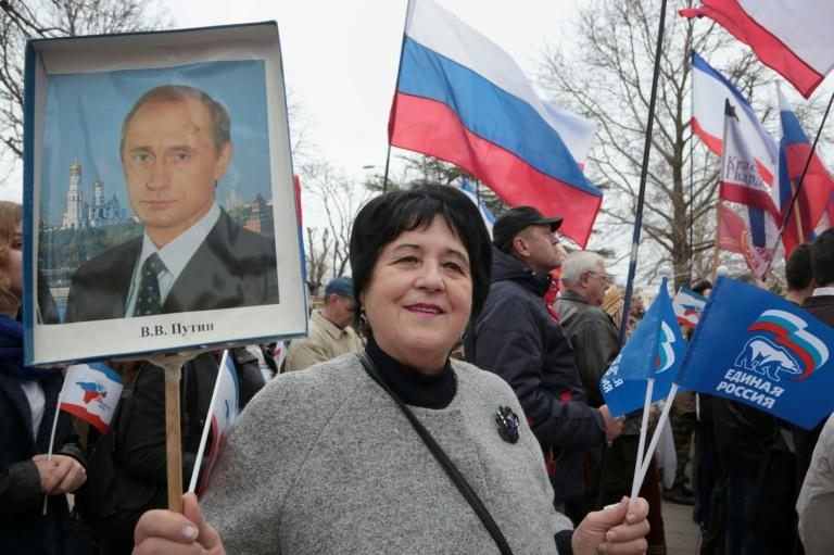 A woman holds a portrait of Russian President Vladimir Putin as she takes part in a rally in Simferopol, on March 16, 2017