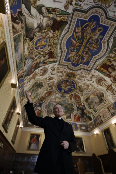 Msgr. Cesare Pasini, prefect of the Vatican Apostolic Library, gestures during an interview with The Associated Press, inside a frescoed hall by 17th century painter Paul Brill, at the Apostolic Library, at the Vatican, Tuesday, Dec. 3, 2013. The Vatican Library and Oxford University's Bodleian Library put the first of 1.5 million pages of ancient manuscripts online Tuesday, bringing their full two-volume Gutenberg Bibles and other precious documents to a global audience for the first time. The two libraries in 2012 announced a four-year project to digitize some of the most important works in their collections of Hebrew manuscripts, Greek manuscripts and early printed books. The 2 million pound ($3.3 million) project is being funded by the Polonsky Foundation, which aims to democratize access to information. (AP Photo/Gregorio Borgia)