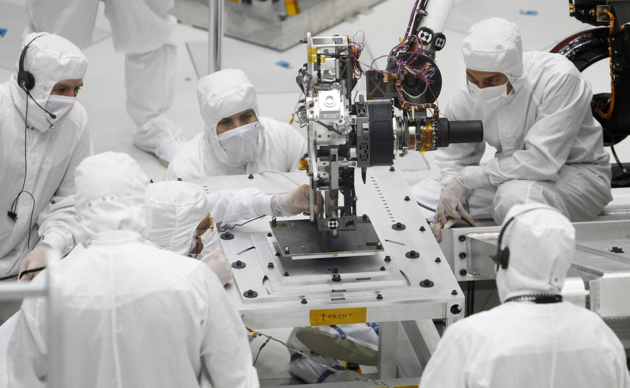 Technicians monitor movement of the robotic arm of NASA's Mars Science Laboratory rover 'Curiosity', where it is undergoing pre-flight tests, in the 'clean room' of the spacecraft assembly facility at the Jet Propulsion Laboratory in Pasadena, California September 16, 2010.  The Mars Science Laboratory rover about the size of a Mini-Cooper automobile, is due to be launched on its mission to Mars late 2011, arriving on Mars in August 2012. REUTERS/Fred Prouser  (UNITED STATES - Tags: SCI TECH)