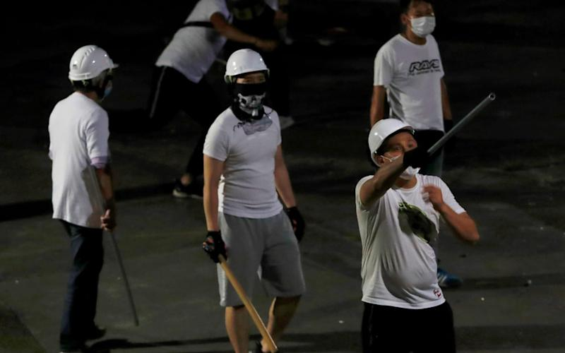 Some of the men in white shirts were filmed leaving the scene in cars bearing Chinese mainland number plates - REUTERS