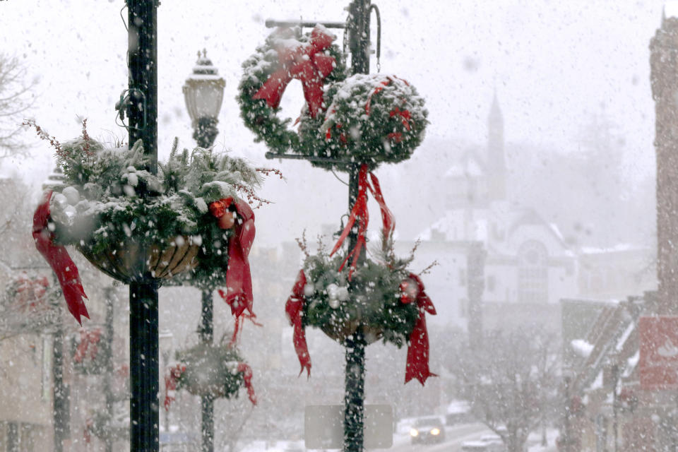 Snow clings to holiday decorations, Saturday, Dec. 5, 2020, in downtown Marlborough, Mass. The northeastern United States is seeing the first big snowstorm of the season. (AP Photo/Bill Sikes)