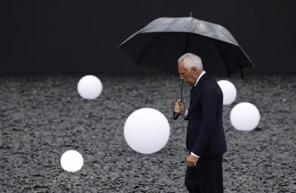 Armani brand founder Giorgio Armani walks outside the venue for his fashion show in Beijing, May 31, 2012. Giorgio Armani, the 77-year-old designer is seeing double digit growth in his business and has no plans just yet to let go of the reins of his eponymous fashion house, he was quoted as saying on May 24. Armani said the company would continue to focus on China where sales grew by 45 percent last year.