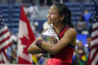 Emma Raducanu, of Britain, hugs the US Open championship trophy after defeating Leylah Fernandez, of Canada, during the women's singles final of the US Open tennis championships, Saturday, Sept. 11, 2021, in New York. (AP Photo/Elise Amendola)