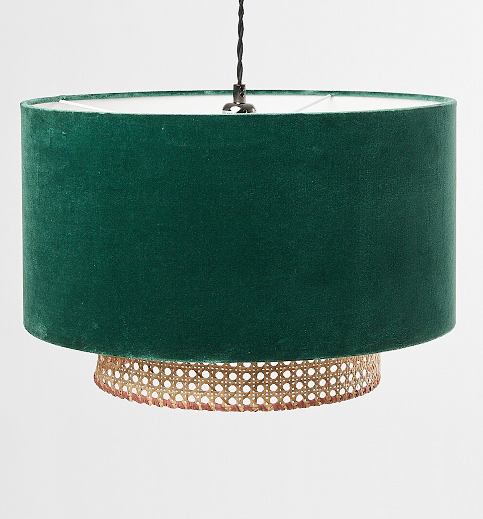 """<p>This is a clever twist on the traditional velvet drum shade. A cane tier peeks from underneath this deep forest green lampshade for a thoroughly contemporary mix of textures. A great choice to soften an extra luxe space. </p><p><strong>Shop now: <a href=""""https://www.oliverbonas.com/homeware/malia-green-velvet-cane-pendant-lamp-shade-328583#selection.color=16"""" rel=""""nofollow noopener"""" target=""""_blank"""" data-ylk=""""slk:Malia Green Velvet & Cane Lamp Shade at Oliver Bonas"""" class=""""link rapid-noclick-resp"""">Malia Green Velvet & Cane Lamp Shade at Oliver Bonas</a></strong></p>"""