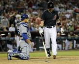Arizona Diamondbacks' Cliff Pennington, right, walks back to pick up his bat after breaking it on home plate during the seventh inning of a baseball game as Los Angeles Dodgers catcher Ramon Hernandez looks on, Saturday, April 13, 2013, in Phoenix. Pennington was ejected from the game for breaking his bat. (AP Photo/Matt York)