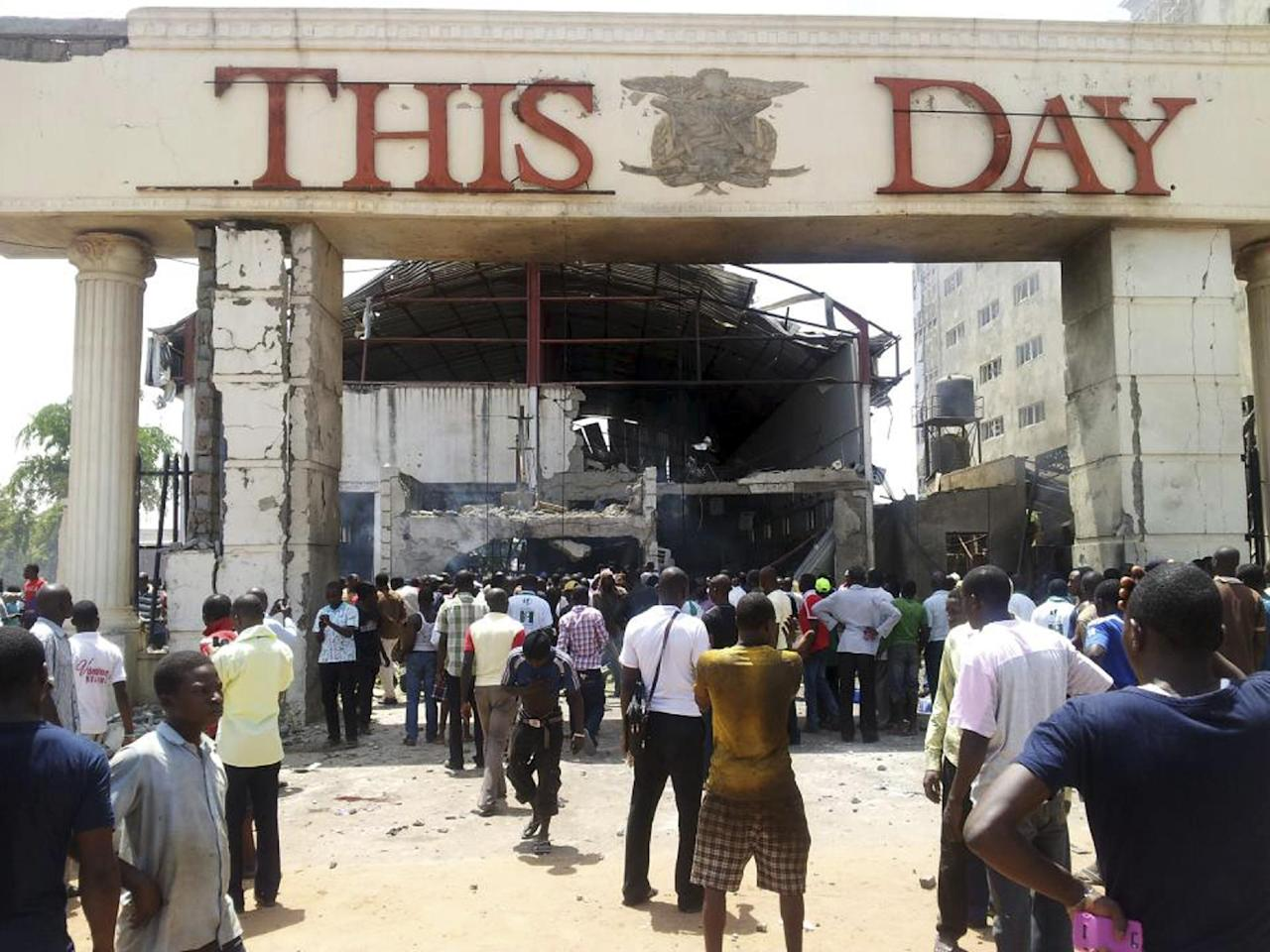 People gather front of the bombed office of ThisDay, an influential daily newspaper in Abuja, Nigeria, Thursday, April. 26, 2012, A suicide bomber detonated a car loaded with explosives Thursday at the office of the major Nigerian newspaper in the country's capital and another man threw a bomb near another newspaper office in Kaduna, killing at least six people in the attacks, witnesses said. (AP Photos/Gbemiga Olamikan)
