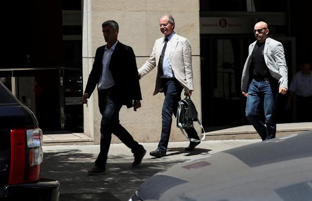Investigating magistrate Joaquin Aguirre is escorted by plainclothes police officers from one of the Catalan public offices which were raided as police investigators raided several Catalan public institutions in search of evidence of alleged misappropriation of public aid money, according to Spanish media, in Barcelona, Spain, May 24, 2018. REUTERS/Albert Gea