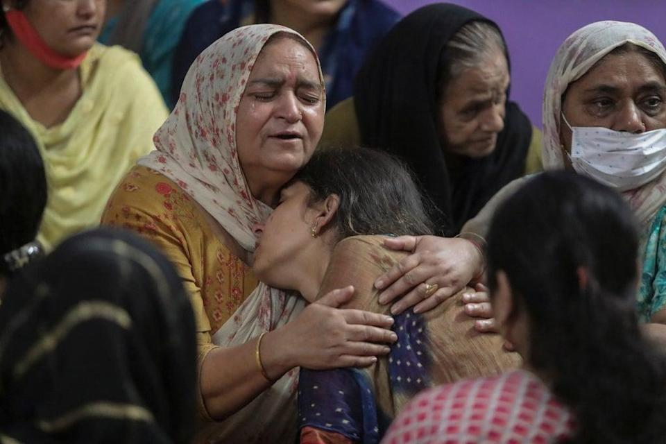 Relatives of Deepak Chand, one of two schoolteachers shot dead by assailants in India's Kashmir on Thursday mourn at their residence (AP)