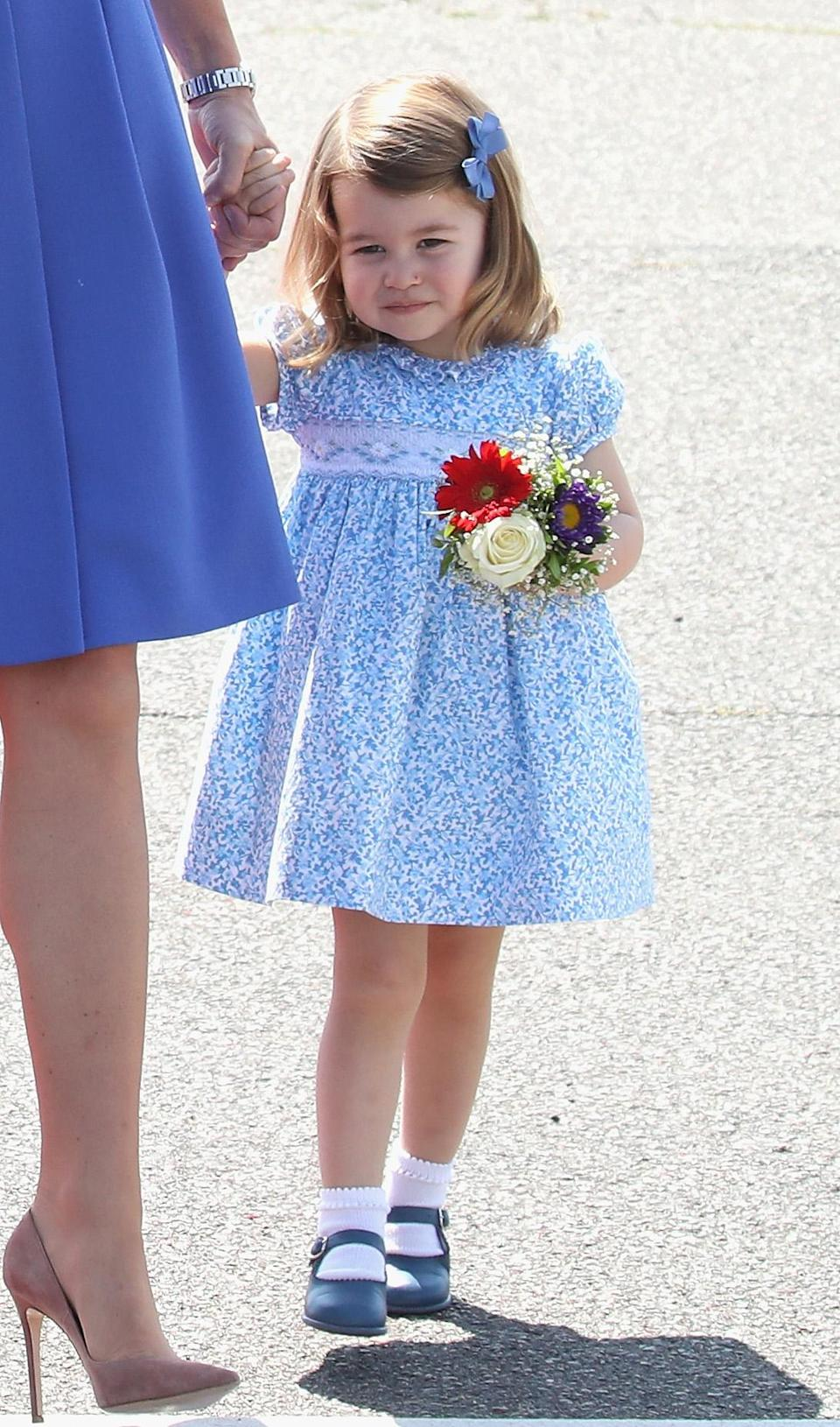 <p>Princess Charlotte carried a bunch of flowers as she arrived at Berlin airport during an official visit to Poland and Germany with her family wearing the cutest blue dress.<br><em>[Photo: Getty]</em> </p>