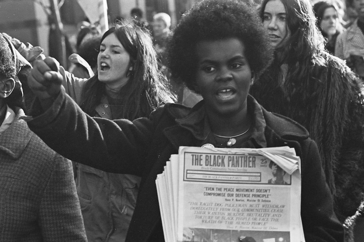 A woman at a rally in support of the Black Panthers, holding copies of The Black Panther newspaper, New Haven, CT, November, 1969.