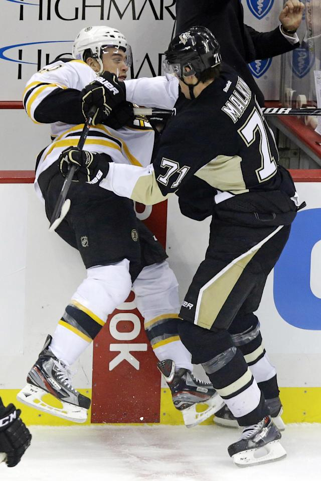 Pittsburgh Penguins' Evgeni Malkin (71) checks Boston Bruins' Daniel Paille (20) into the boards during the first period of an NHL hockey game in Pittsburgh, Wednesday, Oct. 30, 2013. (AP Photo/Gene J. Puskar)