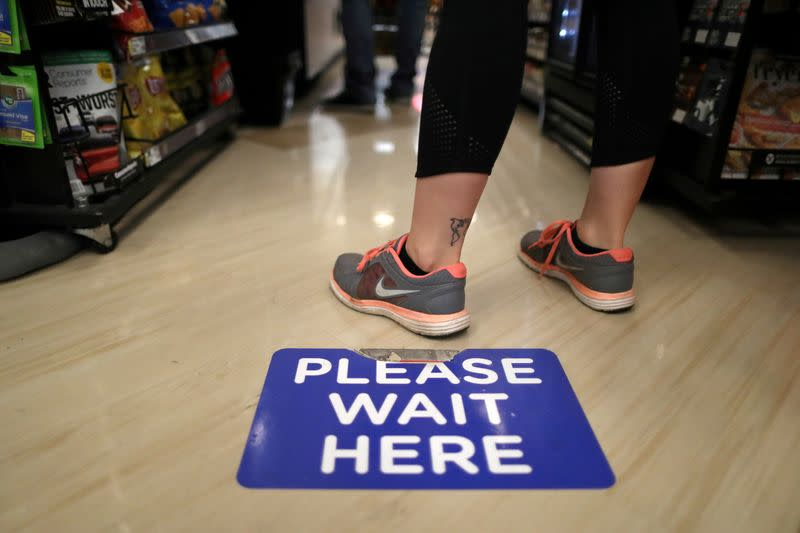 Social distancing decals are seen on the floor of Ralphs Kroger grocery store after California issued a stay-at-home order in an effort to prevent the spread of coronavirus disease (COVID-19), in Los Angeles