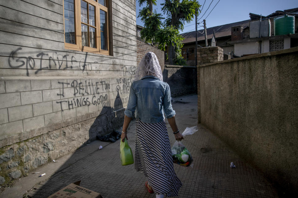 Sabu Sheikh, a transgender Kashmiri, walks homeward after collecting food handouts in Srinagar, Indian controlled Kashmir, Thursday, May 27, 2021. Kashmir's transgender are often only able to find work as matchmakers or wedding entertainment. Prolonged coronavirus lockdowns, preceded by a strict security lockdown in the region in 2019 when India scrapped Kashmir's semi-autonomous status, left many in the transgender community with no work at all. (AP Photo/ Dar Yasin)