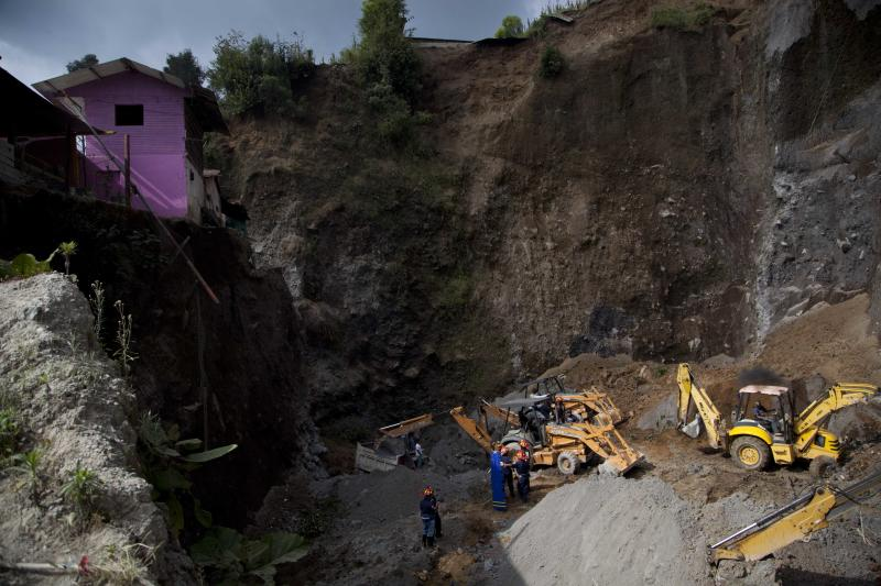 Residents and rescue workers use heavy equipment to look for people feared buried at a sand mine, after a magnitude 7.4 earthquake struck in San Marcos, Guatemala, Wednesday Nov. 7, 2012. The mountain village, some 80 miles (130 kilometers) from the epicenter, suffered much of the damage with some 30 homes collapsing in its center. There are three confirmed dead and many missing after the strongest earthquake to hit Guatemala since a deadly 1976 quake that killed 23,000. (AP Photo/Moises Castillo)