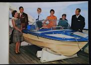 <p>A cheekier card than years past, the 1969 holiday message features the windblown royal family around a speed boat. </p>