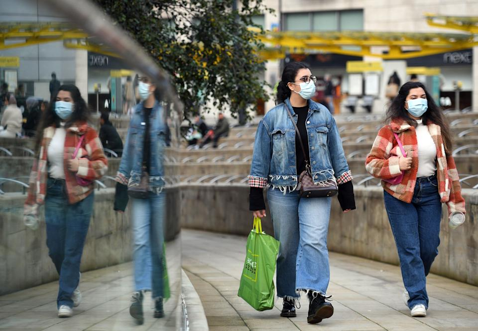 """People wear PPE masks and face coverings as they walk through the city centre in Manchester, north west England on October 8, 2020. - Pubs and restaurants in coronavirus hotspots look set to face fresh restrictions after Downing Street said new data suggests there is """"significant"""" transmission taking place in hospitality settings. A """"range of measures"""" is being looked at, with a particular focus on northern England, where it says infection rates are rising fastest. (Photo by Oli SCARFF / AFP) (Photo by OLI SCARFF/AFP via Getty Images)"""