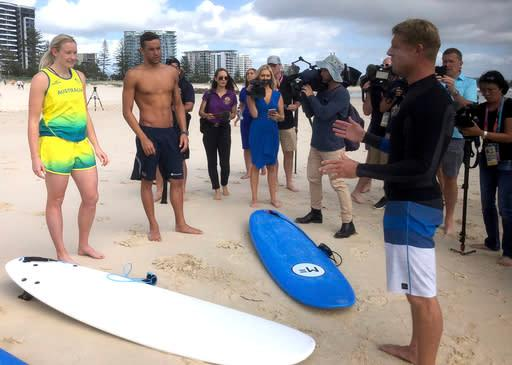 Australian surf legend Mick Fanning , right, talks to South African swimmer Chad Le Clos, right, and Australian para cyclist Jessica Gallagher during a surf lesson at Kirra Beach on the Gold Coast, Australia, Wednesday, April 11, 2018. Le Clos accepted the offer of a surfing lesson at Fanning's local Kirra Beach the morning after completing his swimming program at the Commonwealth Games, where he won five medals for South Africa, with one reservation. He wanted to know if there were any sharks in the water. (AP Photo/John Pye)