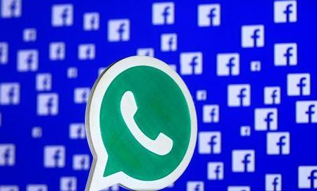 FILE PHOTO: A 3D printed Whatsapp  logo is seen in front of a displayed Facebook logo in this illustration taken