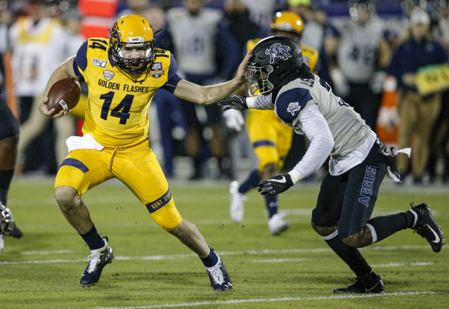Kent State quarterback Dustin Crum (14) carries the ball as Utah State safety Troy Lefeged Jr. (3) defends during the first half of the Frisco Bowl NCAA college football game Friday, Dec. 20, 2019, in Frisco, Texas. (AP Photo/Brandon Wade)