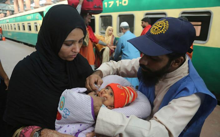A health worker giving a polio vaccination to a child in Lahore railway station, Pakistan - AP