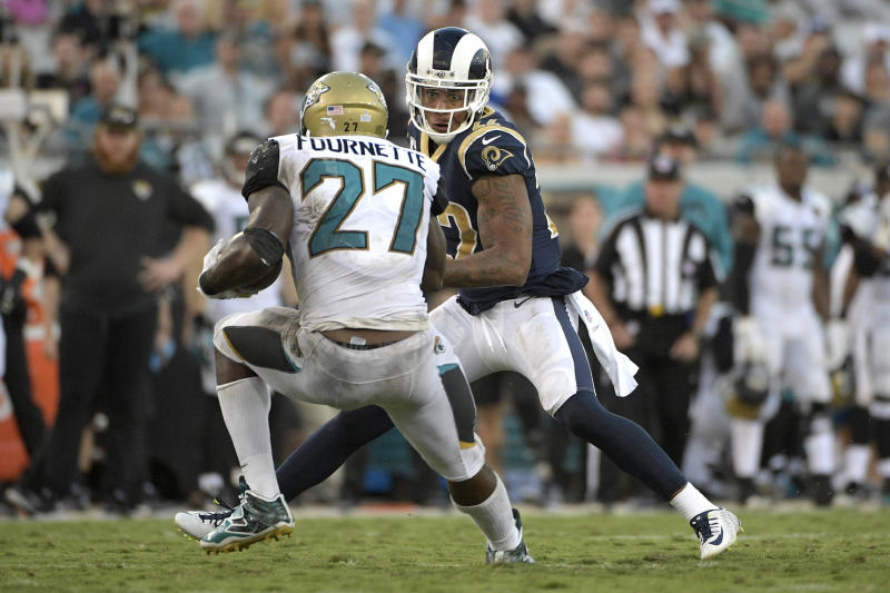 Jaguars running back Leonard Fournette (27) plants his right leg awkwardly in front of Rams cornerback Trumaine Johnson while trying to make a cut. (AP)