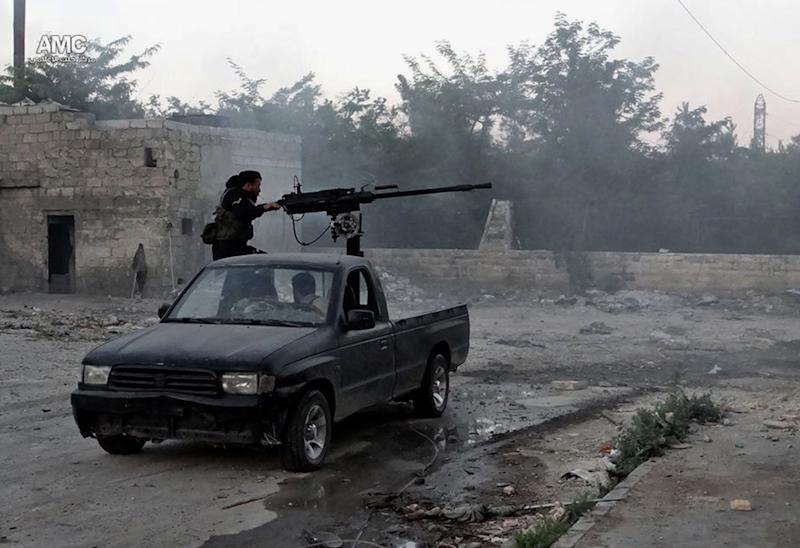 In this Thursday, June 20, 2013 citizen journalism image provided by Aleppo Media Center AMC, which has been authenticated based on its contents and other AP reporting, a Syrian rebel fires a heavy machine gun towards Syrian soldiers loyal to Syrian President Bashar Assad in Aleppo, Syria. Congress is balking at the administration's first attempt to pay for lethal aid to the Syrian rebels until the White House presents a more fully developed proposal than one they received last week from Secretary of State John Kerry, including options for what the U.S. will do next if the initial surge of arms fails to improve the rebels' standing in the civil war that's gone on for more than two years. (AP Photo/Aleppo Media Center AMC)