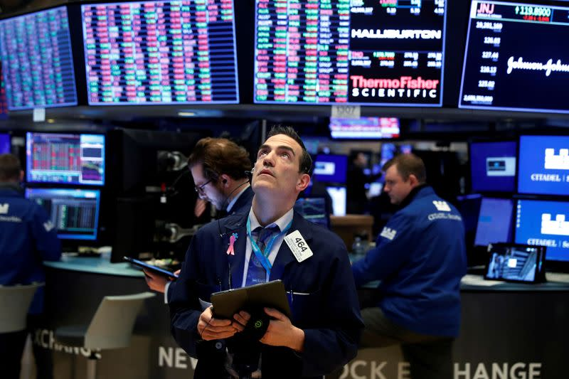 FILE PHOTO: Traders work on the floor of the New York Stock Exchange (NYSE) as the building prepares to close indefinitely due to the coronavirus disease (COVID-19) outbreak in New York