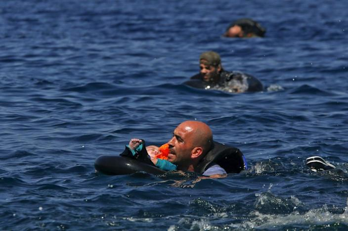 <p>A Syrian refugee holding a baby in a life tube swims toward shore after their dinghy deflated some 100 meters away before reaching the Greek island of Lesbos, Sept. 13, 2015. <i>(Alkis Konstantinidis/Reuters)</i></p>