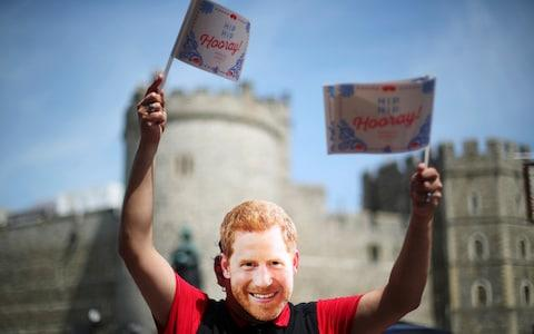 A person wear a Prince Harry mask outside Windsor Castle  - Credit: HANNAH MCKAY /REUTERS