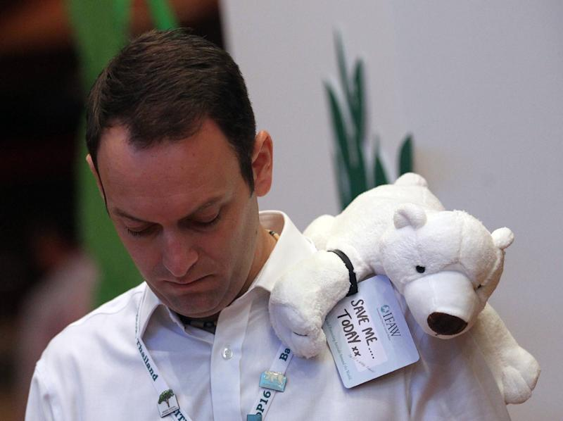 A wildlife organization representative stands with a stuffed polar bear on his shoulder before voting on a proposal by Washington to change the status of the polar bear from a species whose trade is merely regulated, not banned at the Convention on International Trade in Endangered Species, in Bangkok, Thailand Thursday, March 7, 2013. The proposal by the United States to ban cross-border trade in polar bears and their parts was defeated Thursday at an international meeting of conservationists, marking a victory for Canada's indigenous Inuit people over their big neighbor to the south. (AP Photo/Sakchai Lalit)