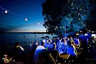 Festival goers take time out from the revelry at Montreux Jazz Festival to relax on the picturesque banks of Lake Geneva.