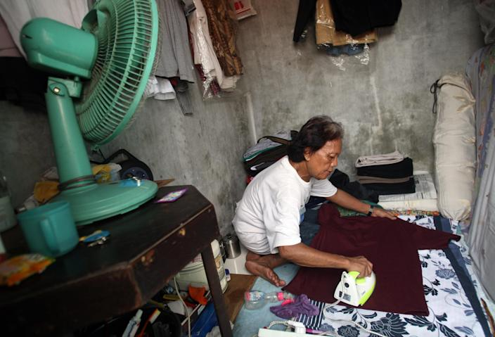 In this Friday, Jan. 27, 2012 photo, Evie, also known as Turdi, the former nanny of U.S. President Barack Obama, irons laundry in her room at a boarding house in a slum in Jakarta, Indonesia. Evie, who was born a man but believes she is really a woman, has endured a lifetime of taunts and beatings because of her identity. Nobody knows how many transgenders live in the sprawling archipelagic nation of 240 million, but activists estimate 7 million. However, societal disdain still runs deep - when transgenders act in TV comedies, they are invariably the brunt of the joke. (AP Photo/Dita Alangkara)