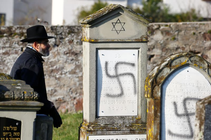 A man walks past graves desecrated with swastikas at the Jewish cemetery in Westhoffen