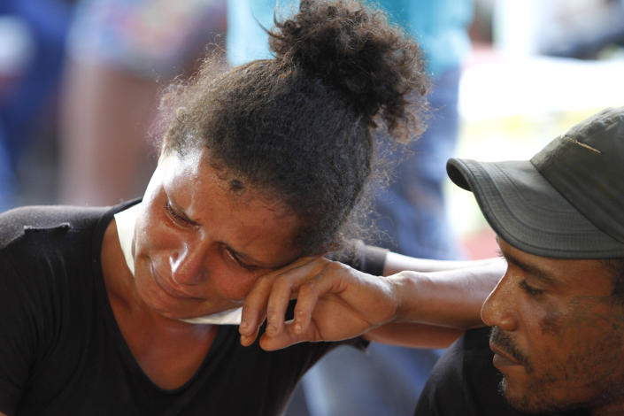 A woman cries as she waits outside the coroner's office in Altamira, Brazil, Tuesday, July 30, 2019. Relatives of inmates killed during a prison riot in northern Brazil gathered at the coroner's office Tuesday to identify the 57 victims, with some passing out at seeing the beheaded corpse of a loved one. (AP Photo/Raimundo Pacco)