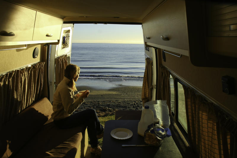 A young woman eats breakfast in an RV parked by the sea.