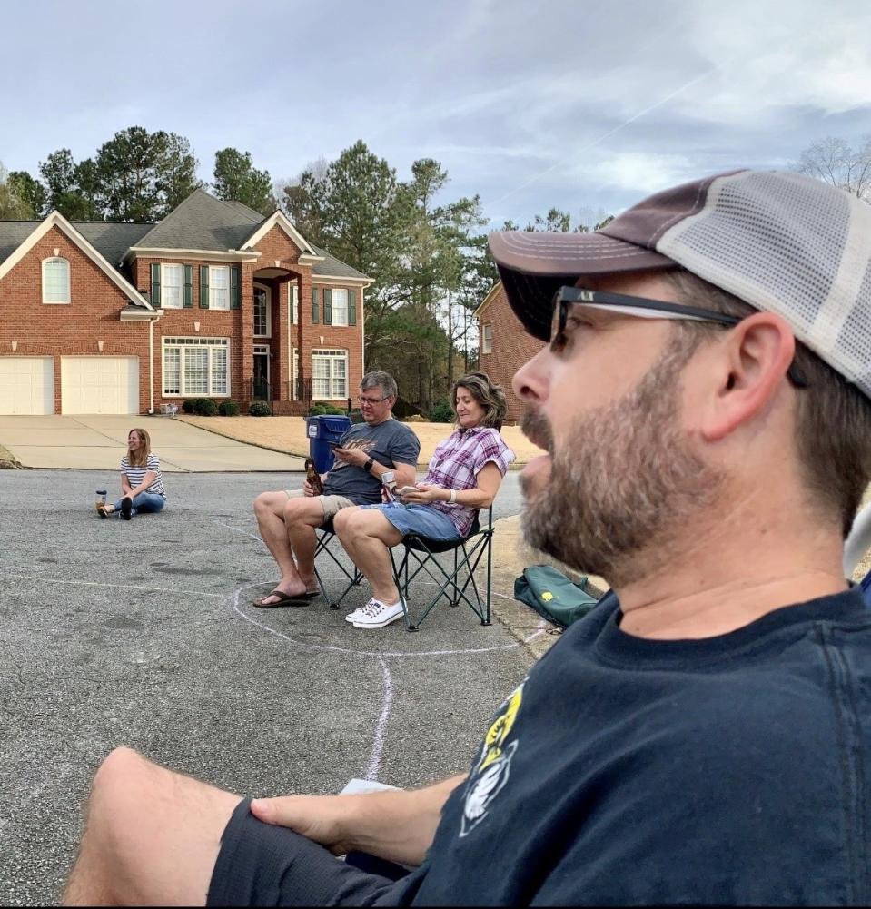 Ken Whitley and neighbors held an impromptu block party on their cul-de-sac in their metro Atlanta neighborhood, sitting in pods that are six feet apart and outlined on the street with chalk. (Credit: Heather Whitley)