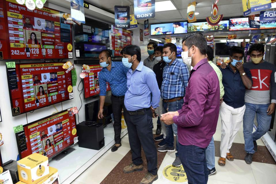 People watch news of Bihar state assembly election results at an electronics shop in Patna, India, Tuesday, Nov. 10, 2020. (AP Photo/Aftab Alam Siddiqui)