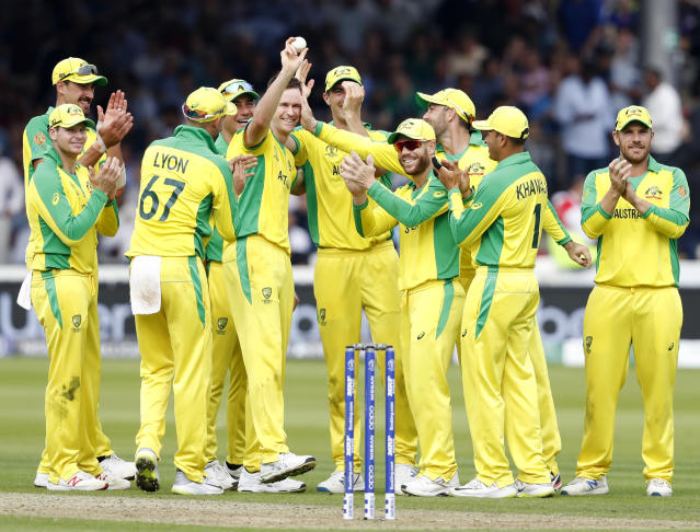 Australia's Jason Behrendorff, centre, holds up the ball as he celebrates with teammates after taking the wicket of England's Jofra Archer during the Cricket World Cup match between England and Australia at Lord's cricket ground in London, Tuesday, June 25, 2019. (AP Photo/Alastair Grant)