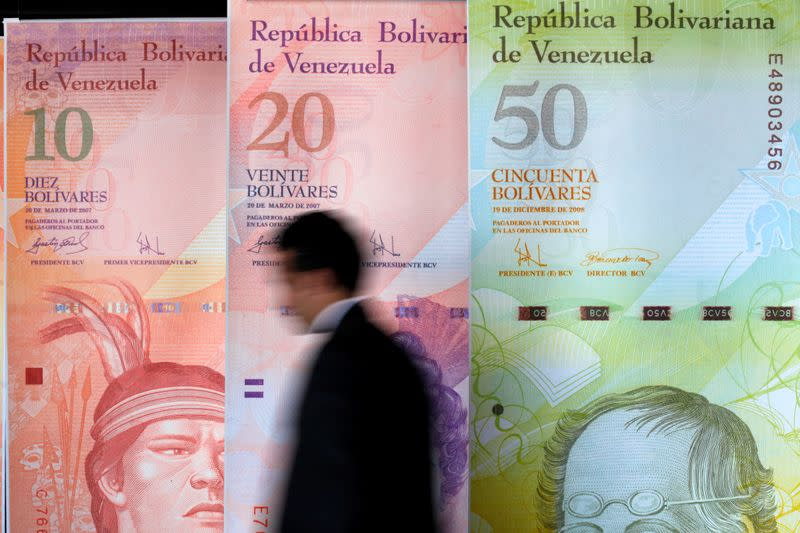 FILE PHOTO: A man walks past big samples of Venezuelan bank notes at the Central Bank headquarters in Caracas