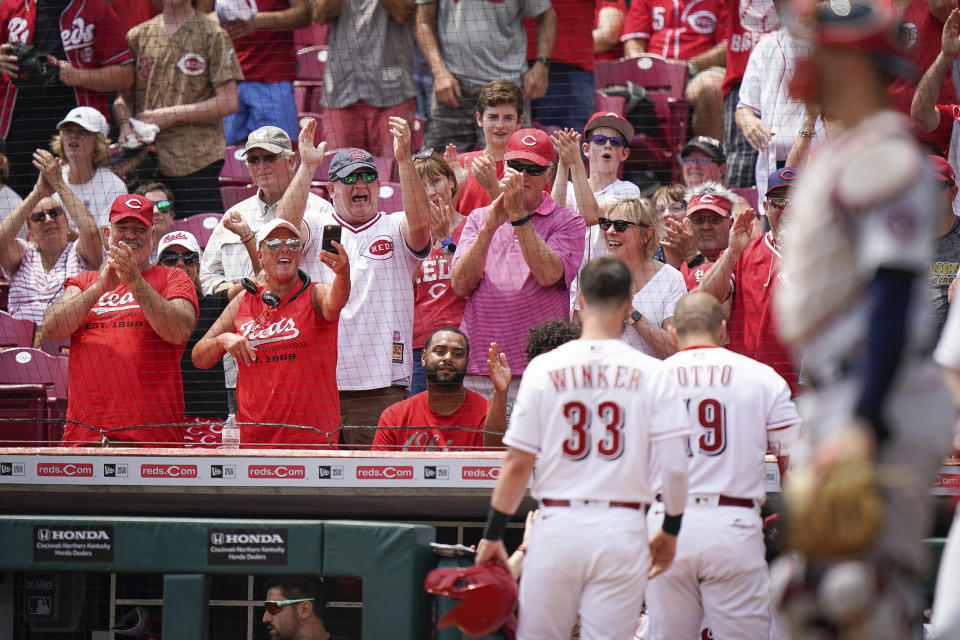 Fans celebrate after Cincinnati Reds' Joey Votto (19) hit a three run home run during the first inning of a baseball game against the St. Louis Cardinals in Cincinnati, Sunday, July 25, 2021. (AP Photo/Bryan Woolston)