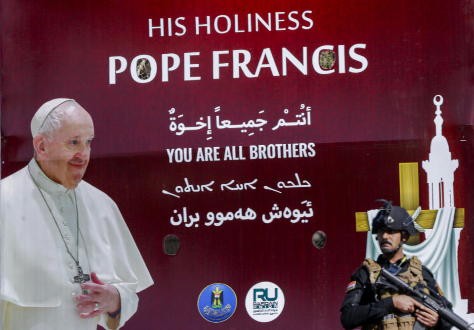 Iraqi security stand by a poster depicting Pope Francis, in Baghdad Iraq, Friday, March 5, 2021. Pope Francis heads to Iraq on Friday to urge the country's dwindling number of Christians to stay put and help rebuild the country after years of war and persecution, brushing aside the coronavirus pandemic and security concerns. (AP Photo/Andrew Medichini)